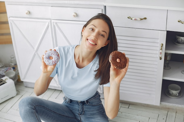 Mooi meisje dat zich in een keuken met doughnut bevindt