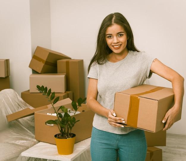 Mooi meisje dat zich met doos in nieuw huis bevindt