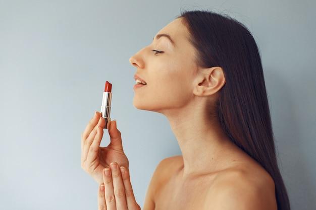 Mooi meisje dat zich met rode lippenstift bevindt