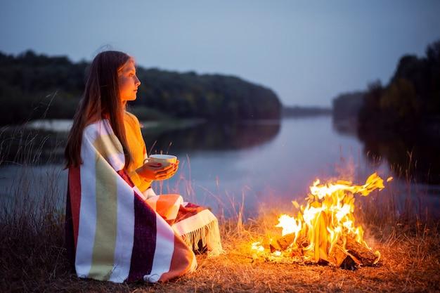 Mooi meisje dat zichzelf opwarmt bij het vuur, gestreepte deken en thee zittend aan de oever van de rivier. kamperen in de natuur, rustconcept.