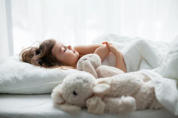 Mooi meisje dat zoet in een wit bed slaapt met konijnenspeelgoed dat dichtbij ligt