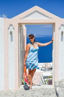 Mooi meisje dichtbij de boog in santorini-eiland (griekenland)