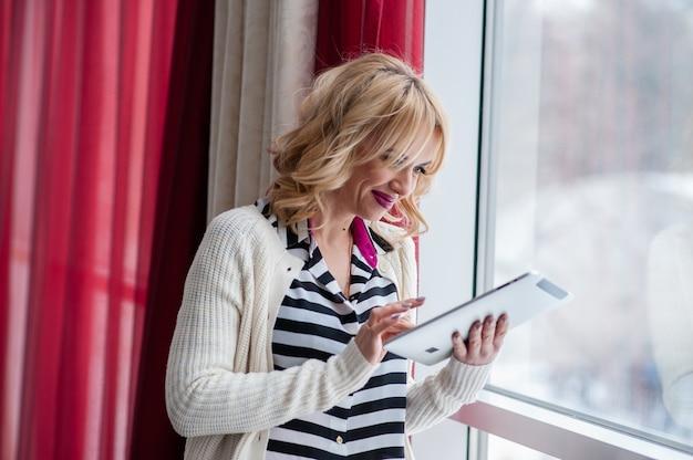 Mooi meisje dichtbij het venster, blond, laptop