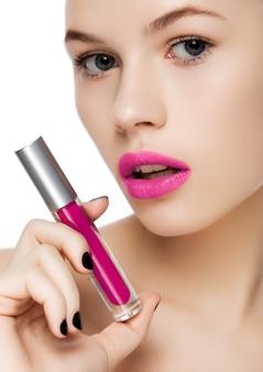 Mooi meisje die de vloeibare violette purpere purpere buis van de lippenstiftcontainer op witte achtergrond houden