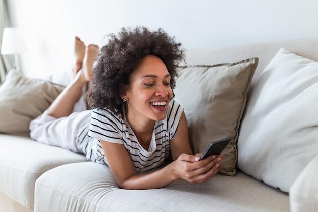 Mooi meisje die haar smartphone op laag thuis in de woonkamer gebruiken.