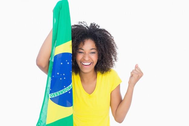 Mooi meisje die in gele t-shirt braziliaanse vlag houden die bij camera glimlachen