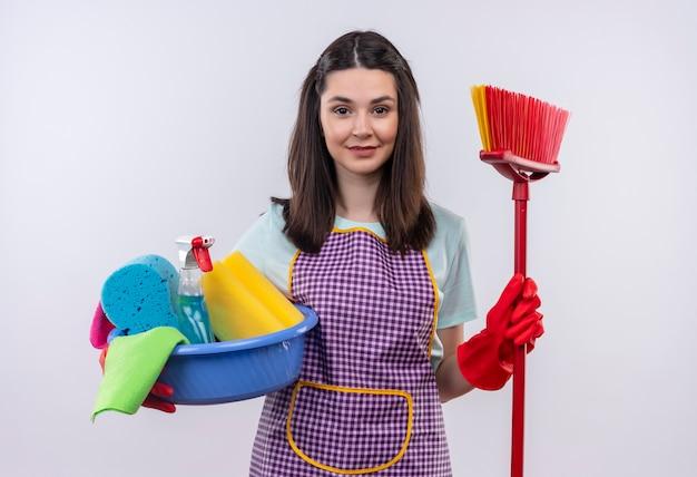 Mooi meisje die in schort en rubberhandschoenen bassin met schoonmakende hulpmiddelen houden en zelfverzekerd glimlachen dweilen