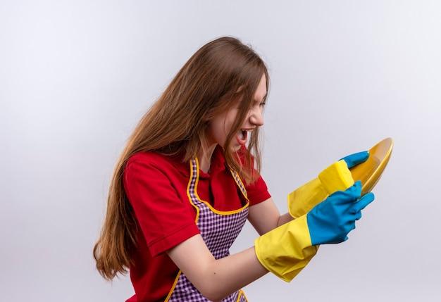 Mooi meisje die in schort en rubberhandschoenen plaat houden die met agressieve uitdrukking schreeuwen
