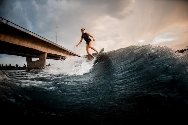 Mooi meisje die op wakeboard op de rivier op de achtergrond van de brug berijden