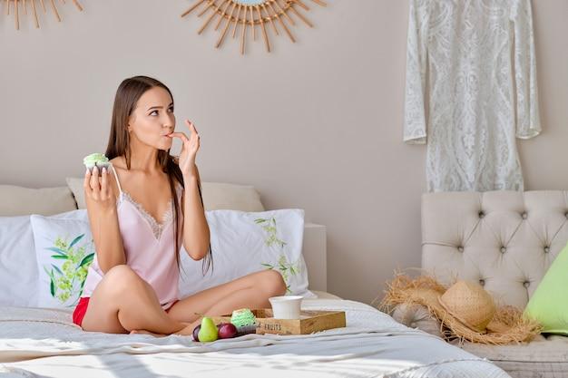 Mooi meisje die vinger likken terwijl het hebben van snack in bed op weekend