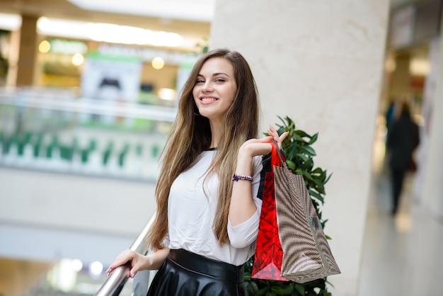 Mooi meisje doet een aankoop in het winkelcentrum.