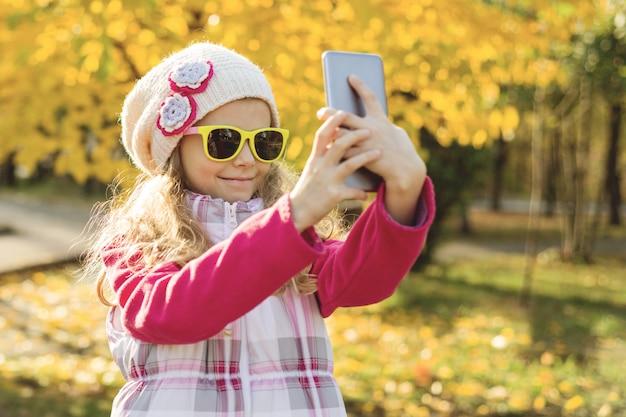 Mooi meisje doet selfie met behulp van smartphone, herfst achtergrond.