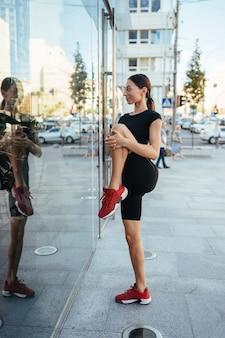Mooi meisje doet zich het uitrekken voor een modern gebouw. het meisje wordt weerspiegeld in de glazen panelen