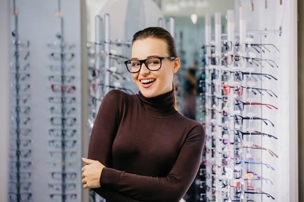 Mooi meisje draagt een bril lachend in de buurt van de stand