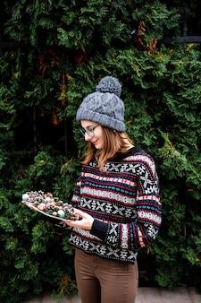Mooi meisje draagt gezellige trui met ornament houdt kleurrijke handgemaakte kerstkrans met kegels en glinsterende ballen in haar handen