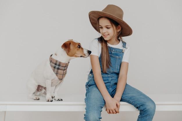 Mooi meisje draagt stijlvolle hoed, wit t-shirt en denim overall, kijkt naar haar puppy, speelt met huisdier