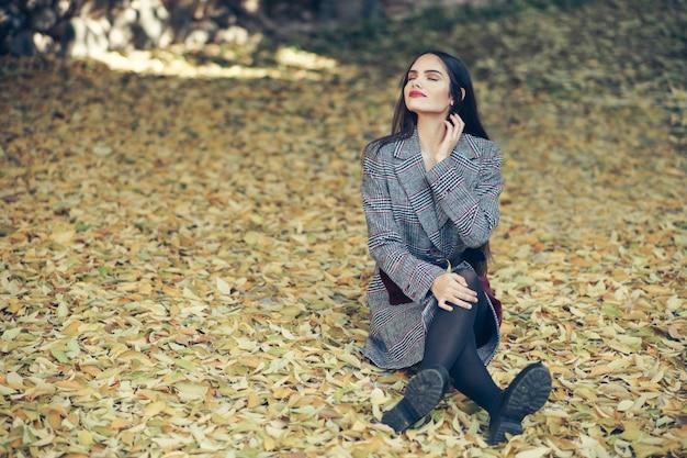 Mooi meisje draagt winterjas zittend op de vloer van een stadspark vol herfstbladeren.