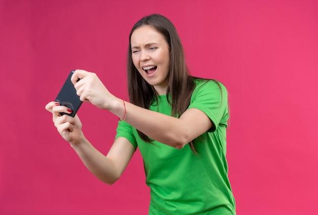 Mooi meisje dragen groene t-shirt met smartphone kijken ernaar gestrest en nerveus staande over geïsoleerde roze achtergrond