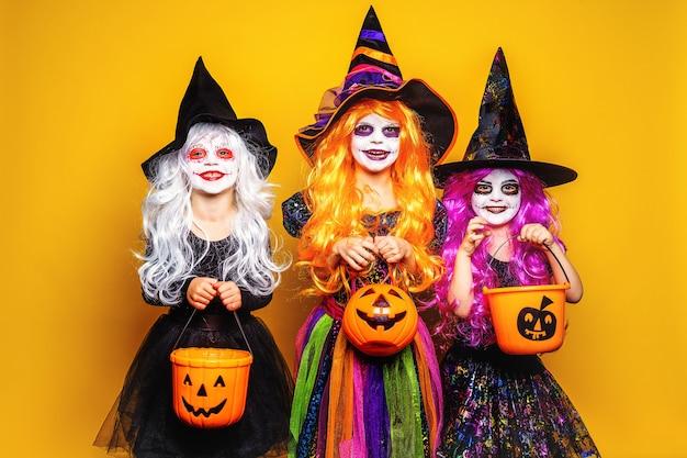 Mooi meisje drie in een heksenkostuum die en gezichten doen schrikken maken