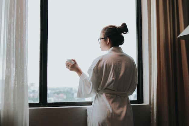 Mooi meisje drinkt een kopje koffie in de ochtend in het hotel