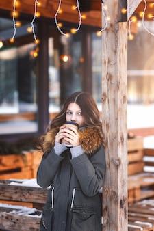 Mooi meisje drinkt koffie op het open terras van het café op een koele avond