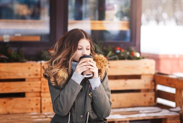Mooi meisje drinkt koffie uit een papieren beker op de veranda van het café