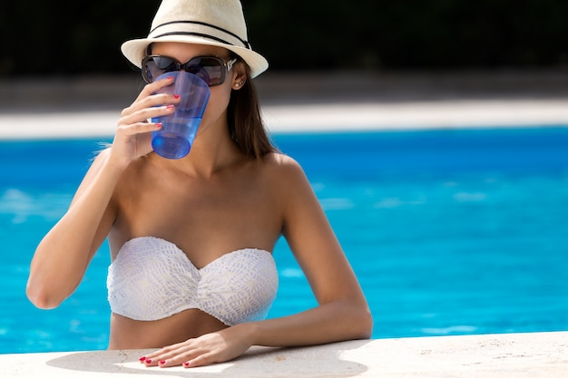 Mooi meisje drinkwater bij het zwembad.