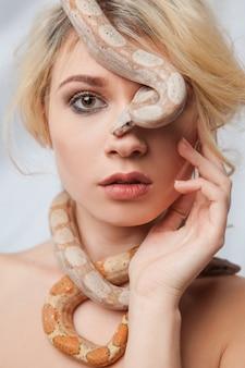 Mooi meisje en de slang boa constrictors, die zich om haar gezicht wikkelt