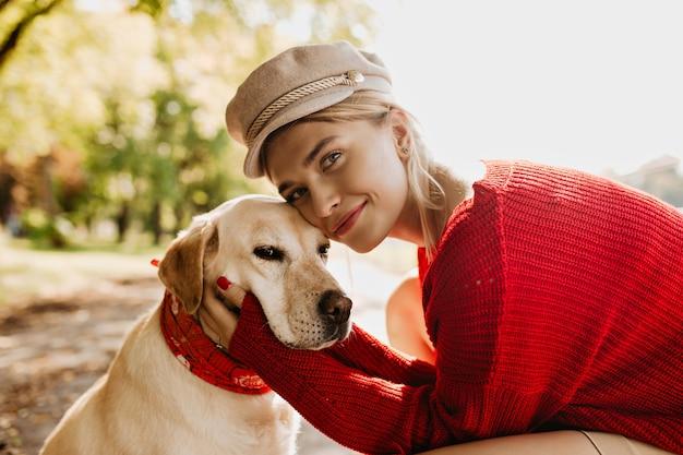 Mooi meisje en haar hond samen met liefde. charmante blonde vrouw met haar huisdier genieten van zonnige herfstdag.