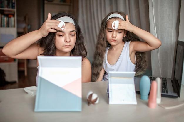 Mooi meisje en haar moeder schoonheid masterclass met tabletten online kijken en spa-procedure zelf doen, moeder en dochter plezier met glad masker op gezicht, schoonheidssalon thuis