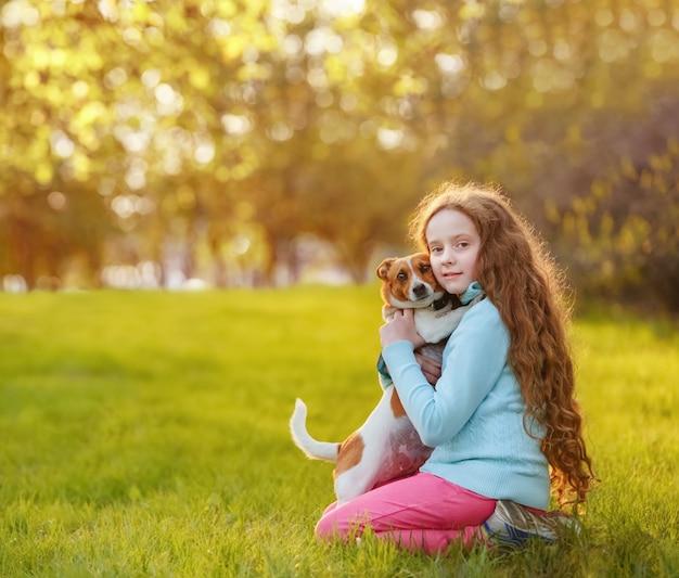 Mooi meisje en haar schattige hond omarmen in het voorjaar van buiten.