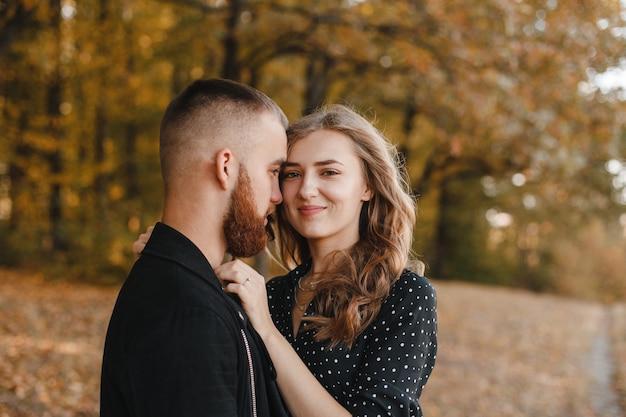 Mooi meisje en jongen met een baard in herfst bos