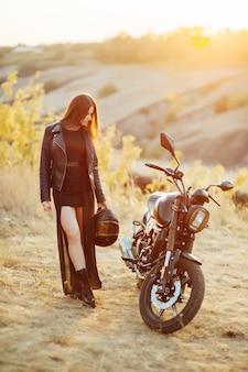 Mooi meisje fietser in zwarte kleding staat op de motorfiets met een veiligheidshelm in zijn handen.