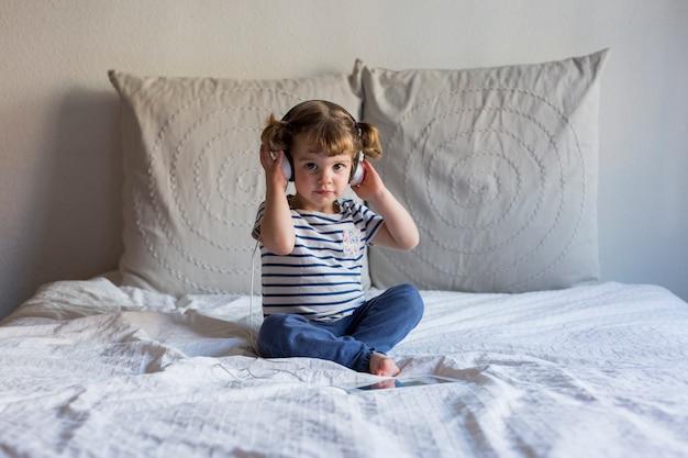 Mooi meisje gebruikend tablet en luisterend aan muziek op hoofdtelefoon op bed. thuis, binnenshuis. lifestyle
