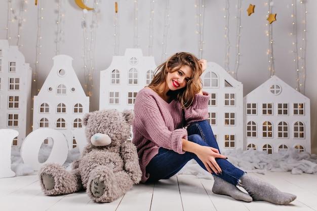 Mooi meisje gekleed in warme trui en spijkerbroek zittend op de vloer met haar grijze teddybeer