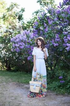 Mooi meisje geniet van de geur van lila op zomerdag mooie vrouw in een blauwe lange vintage jurk staat in een lila tuin