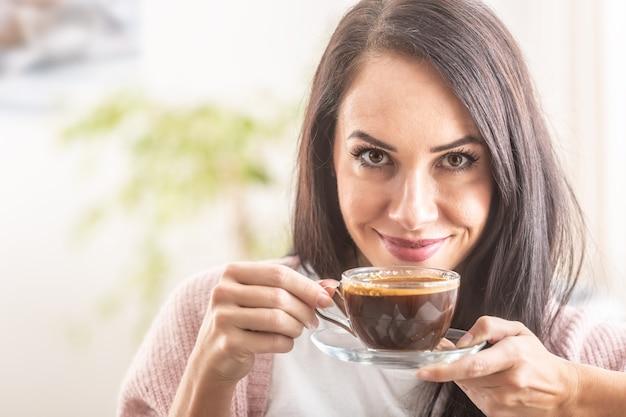 Mooi meisje geniet van de geur van vers gemaakte koffie.