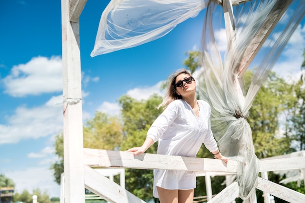Mooi meisje geniet van de natuur op zonnige dag in witte houten prieel in de buurt van het meer. vrijheid