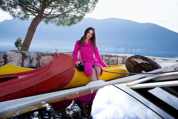 Mooi meisje geniet van prachtig uitzicht op zee. de voorkant van de boot en de bergen. rust alleen met de natuur.