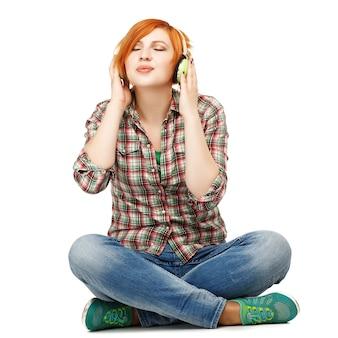 Mooi meisje genieten van het luisteren naar muziek op koptelefoon geïsoleerd op wit