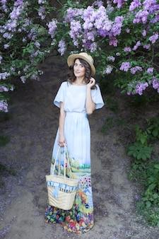 Mooi meisje genieten van lila op zomerdag jonge vrouw in jurk in lila tuin