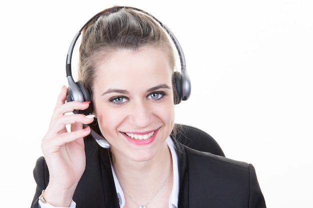 Mooi meisje glimlachend teleoperator met hoofdtelefoon op hoofd