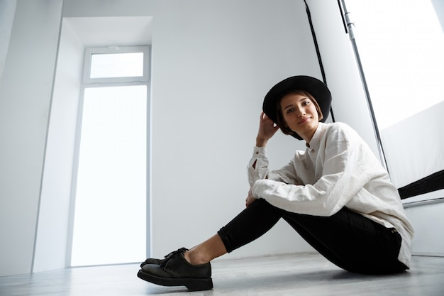 Mooi meisje glimlachend zittend op de vloer over witte muur.