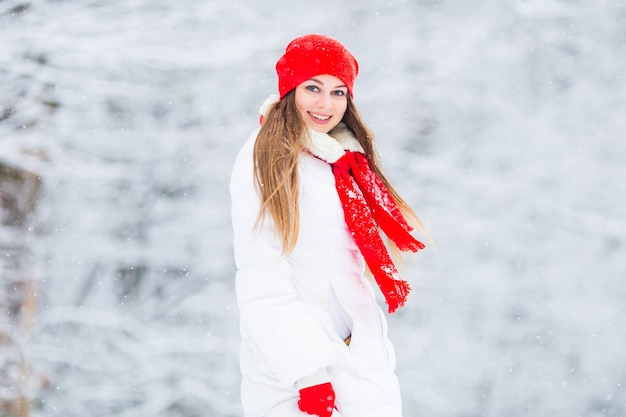 Mooi meisje glimlacht en kijkt naar de camera tegen de achtergrond van vallende sneeuw