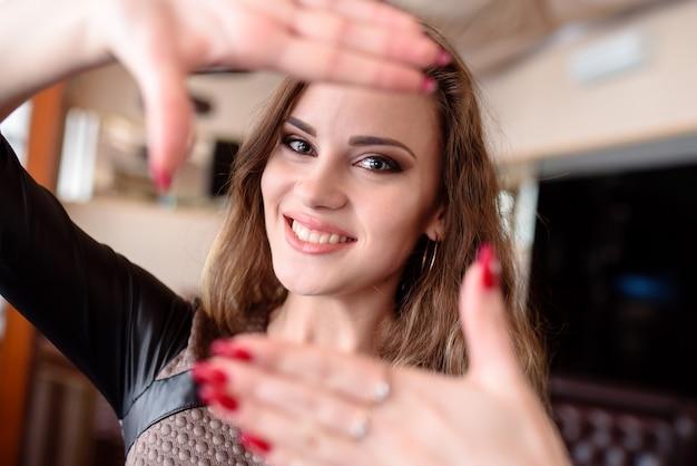 Mooi meisje glimlacht en trekt de handen naar de camera.