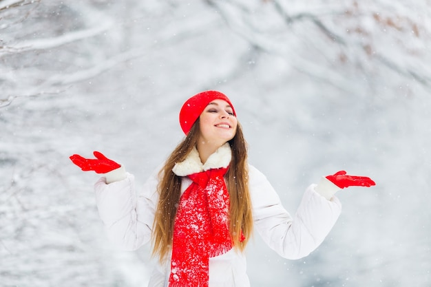 Mooi meisje houdt de handpalmen omhoog en geniet van de sfeer in het winterpark