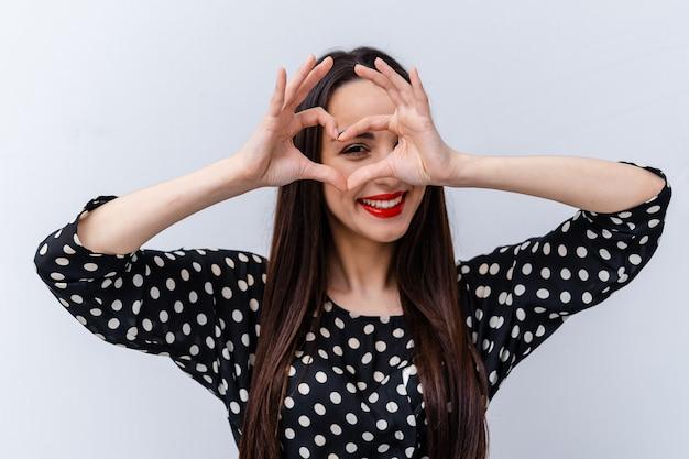 Mooi meisje houdt handen in hartvorm in de buurt van ogen. gestippelde blouse. witte achtergrond.