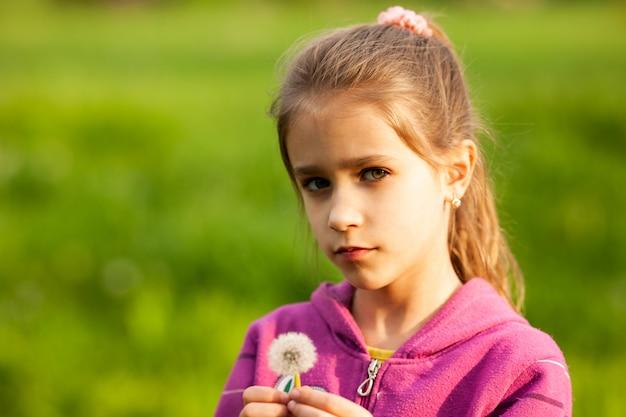 Mooi meisje houdt voorjaar paardebloem in haar hand