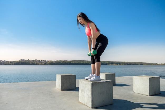 Mooi meisje houdt zich bezig met ochtendgymnastiek met halters aan het meer