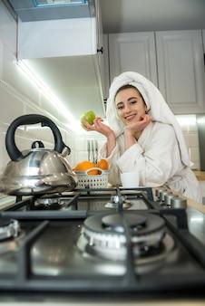 Mooi meisje in badjas na douche kiest vers fruit bij het ontbijt